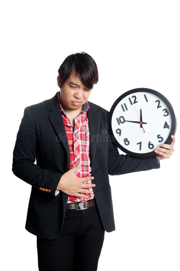El hombre asiático hace que el mún hábito alimentario consiga el dolor de estómago con el reloj imagen de archivo