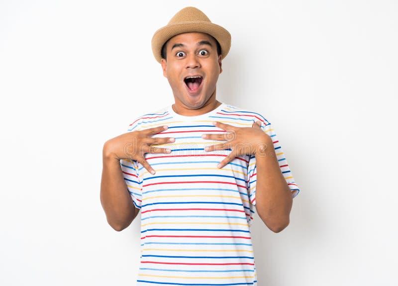 El hombre asiático joven con el sombrero siente choque y sorpresa con excesivamente la expresión de la cara foto de archivo