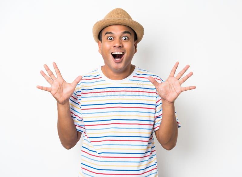 El hombre asiático joven con el sombrero siente choque y sorpresa con excesivamente la expresión de la cara foto de archivo libre de regalías
