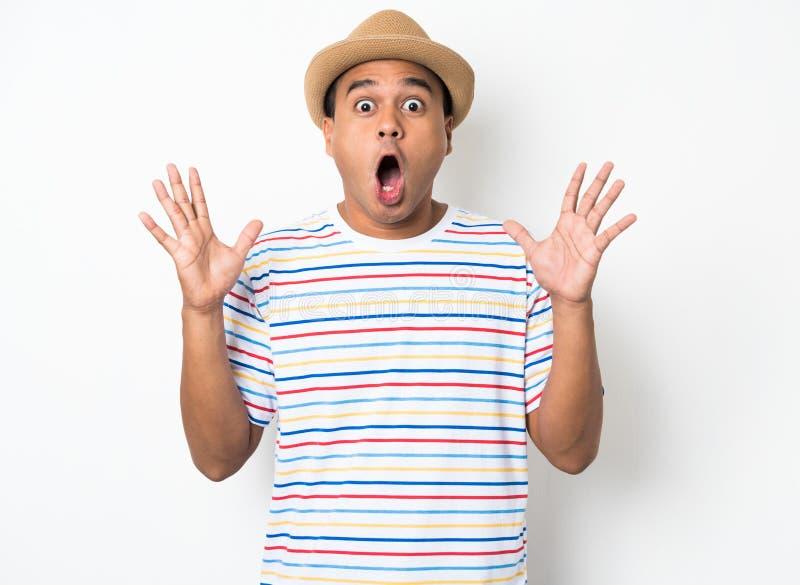 El hombre asiático joven con el sombrero siente choque y sorpresa con excesivamente la expresión de la cara imagen de archivo libre de regalías
