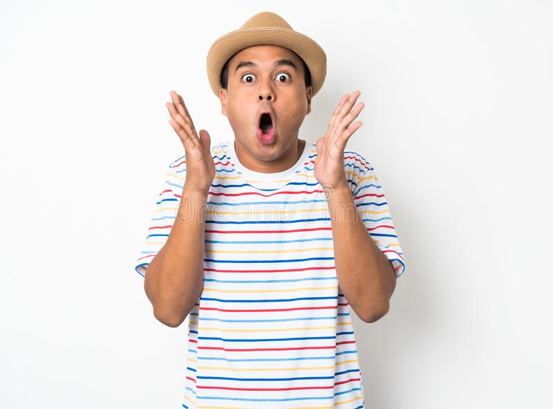 El hombre asiático joven con el sombrero siente choque y sorpresa con excesivamente la expresión de la cara fotografía de archivo
