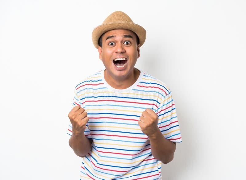 El hombre asiático joven con el sombrero siente choque y sorpresa con excesivamente la expresión de la cara imagenes de archivo