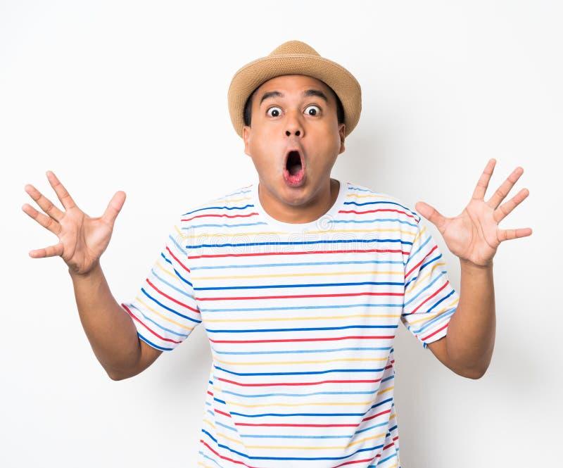 El hombre asiático joven con el sombrero siente choque y sorpresa con excesivamente la expresión de la cara imágenes de archivo libres de regalías