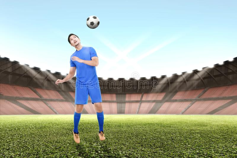 El hombre asiático joven del jugador de fútbol salta y dirigiendo la bola imagen de archivo libre de regalías