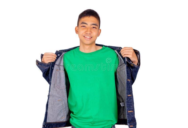 El hombre asiático joven en camiseta verde está poniendo en la chaqueta de los vaqueros imagen de archivo libre de regalías