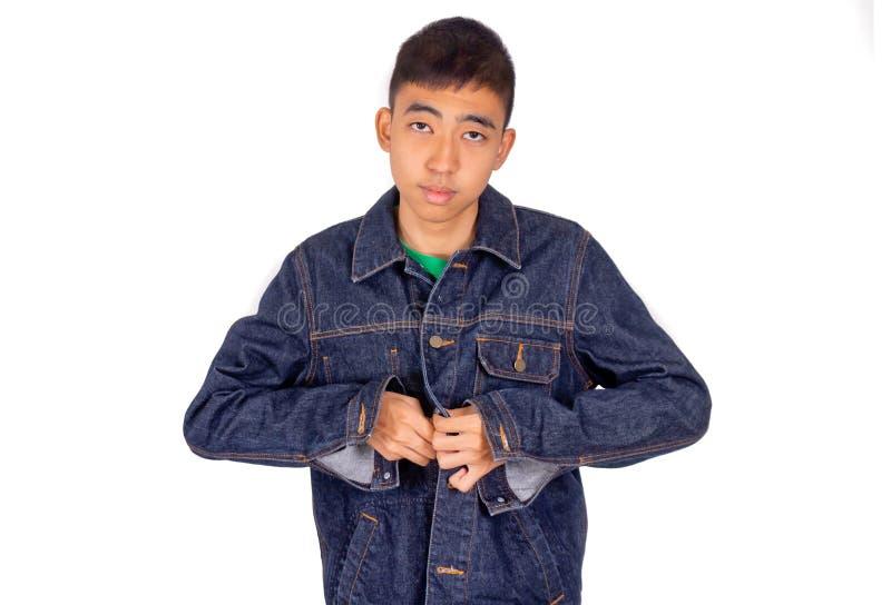 El hombre asiático joven en camiseta verde está poniendo en la chaqueta de los vaqueros foto de archivo