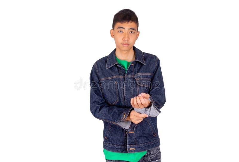El hombre asiático joven en camiseta verde está poniendo en la chaqueta de los vaqueros imagen de archivo