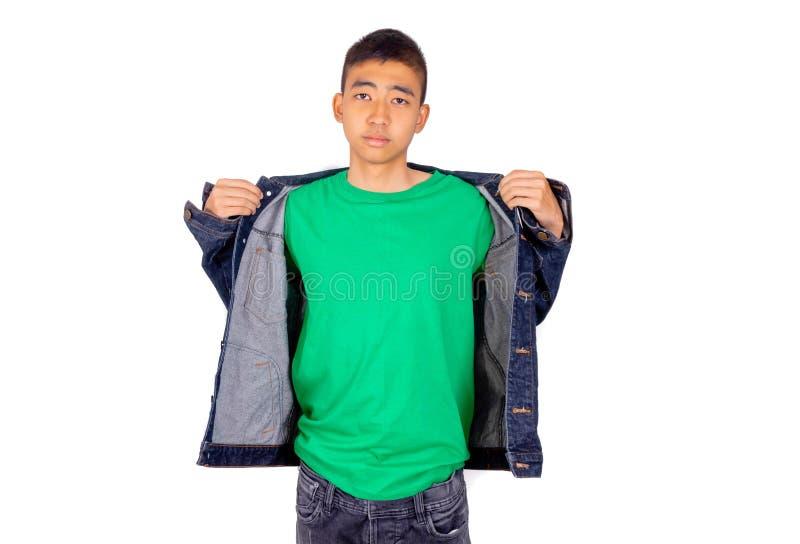 El hombre asiático joven en camiseta verde está poniendo en la chaqueta de los vaqueros imágenes de archivo libres de regalías