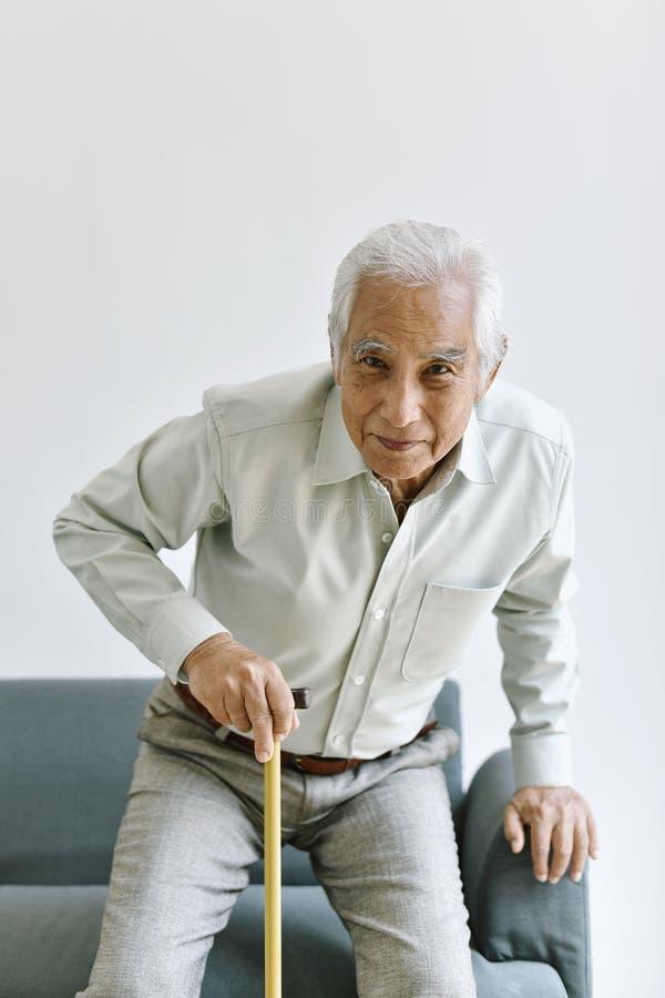 El hombre asiático mayor de la neutralización y de lesión intenta levantarse con el bastón que camina, el dolor de la rodilla y l foto de archivo libre de regalías