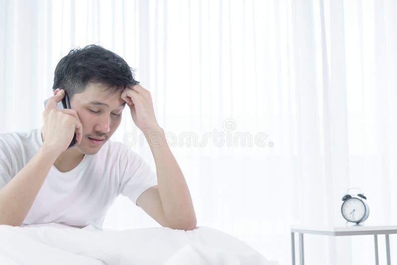 El hombre asiático tiene despertar con hablar de trabajo antes del comienzo que trabaja en cama en la mañana fotografía de archivo libre de regalías