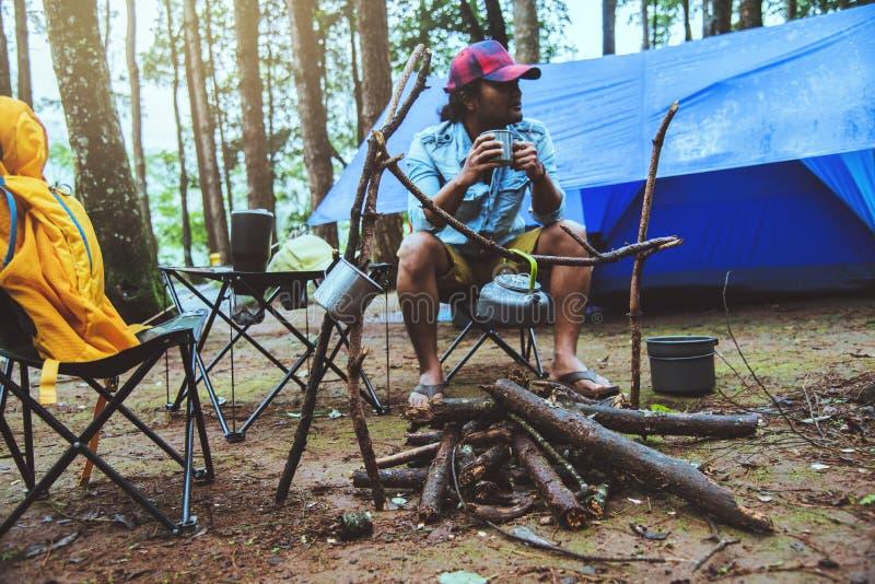El hombre asi?tico relaja la naturaleza del viaje en el d?a de fiesta el acampar y café de la bebida del agua de la ebullición en fotos de archivo