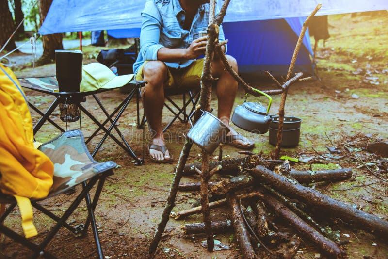 El hombre asi?tico relaja la naturaleza del viaje en el d?a de fiesta el acampar y café de la bebida del agua de la ebullición en foto de archivo libre de regalías