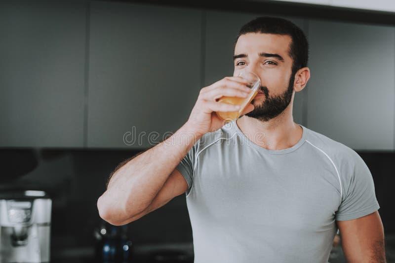 El hombre atlético bebe a Juice On The Kitchen fresco foto de archivo