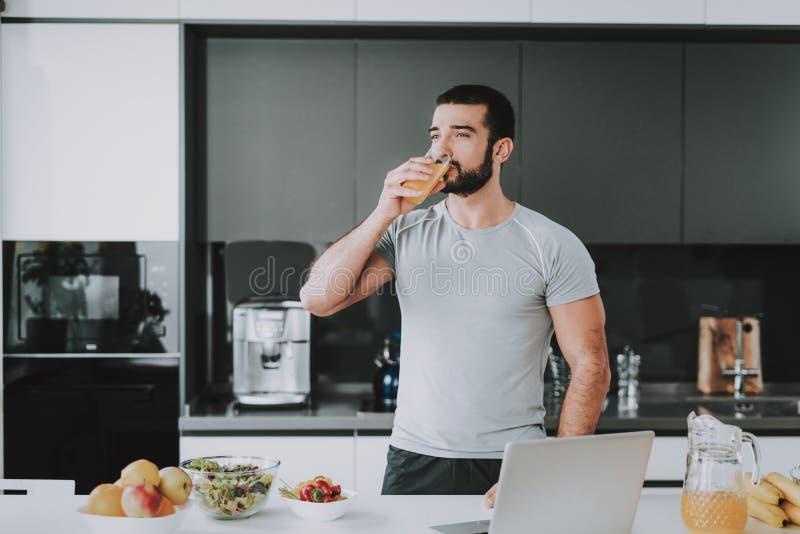 El hombre atlético bebe a Juice On The Kitchen fresco imagen de archivo