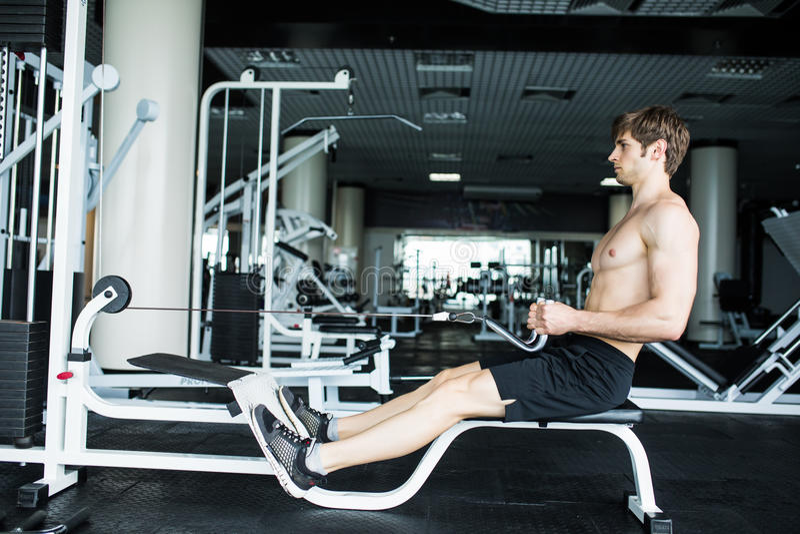 El hombre atlético brutal que bombea para arriba muscles en la cruce Hombre muscular que se resuelve en el gimnasio que hace ejer fotos de archivo