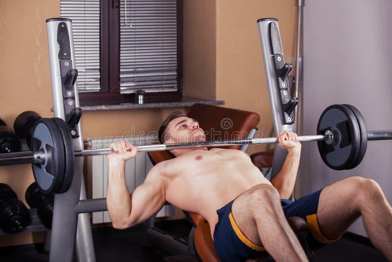 El hombre atlético brutal que bombea para arriba muscles en la prensa de banco imagenes de archivo