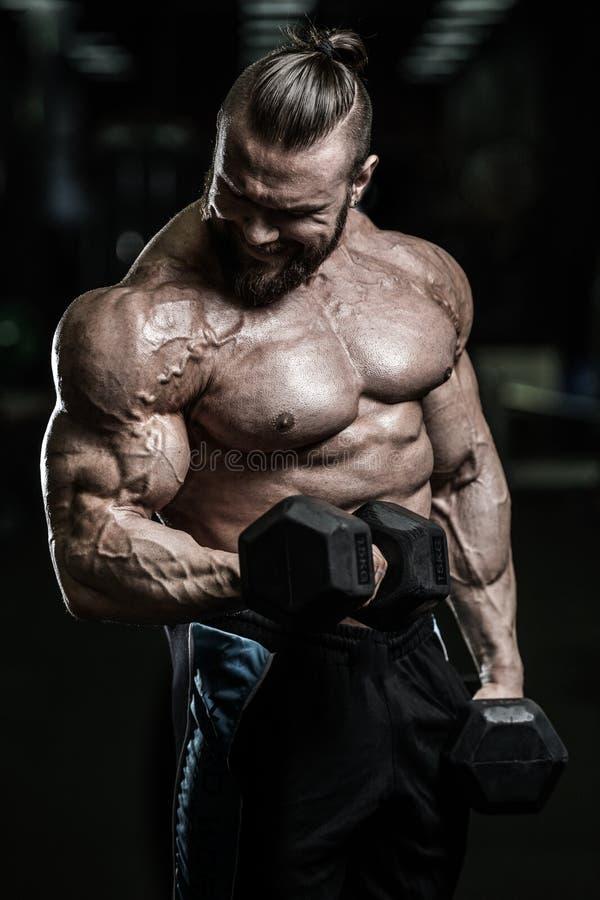 El hombre atlético del poder hermoso en el entrenamiento de la dieta que bombea para arriba muscles imagenes de archivo
