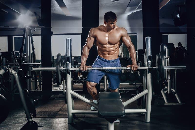 El hombre atlético del poder hermoso en el entrenamiento de la dieta que bombea para arriba muscles con pesa de gimnasia y el bar foto de archivo libre de regalías
