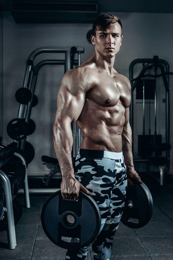 El hombre atlético del poder hermoso en el entrenamiento de la dieta que bombea para arriba muscles con pesa de gimnasia y el bar fotos de archivo libres de regalías