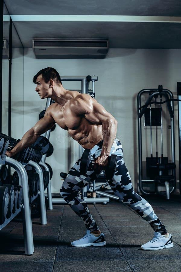 El hombre atlético del poder hermoso en el entrenamiento de la dieta que bombea para arriba muscles con pesa de gimnasia y el bar imagen de archivo