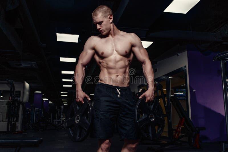 El hombre atlético fuerte hermoso que bombea para arriba muscles con pesas de gimnasia Culturista muscular con el torso desnudo d imágenes de archivo libres de regalías