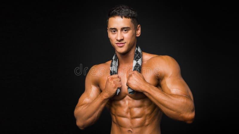 El hombre atlético fuerte muestra el cuerpo y los músculos abdominales sobre fondo gris foto de archivo