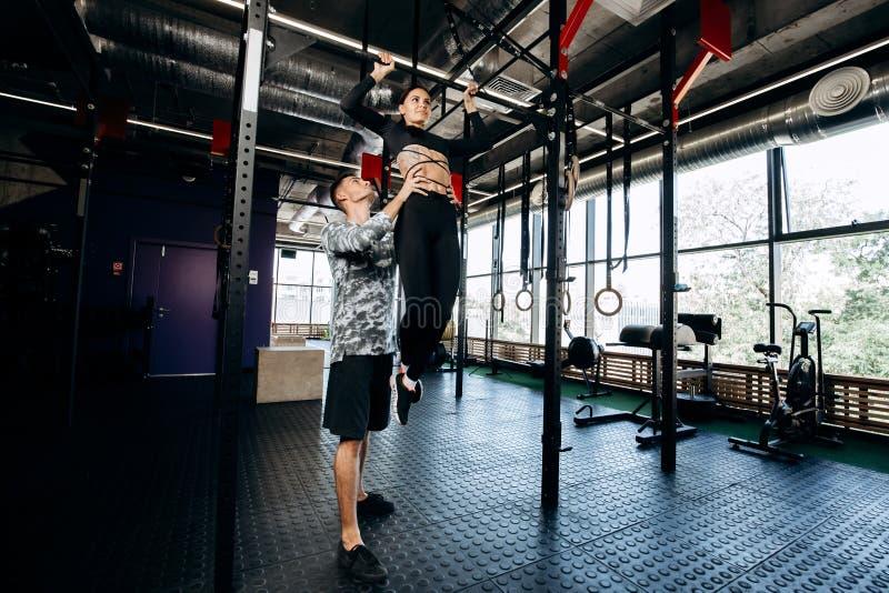 El hombre atlético joven ayuda a la muchacha bonita delgada a hacer levanta en la barra en el gimnasio fotografía de archivo libre de regalías