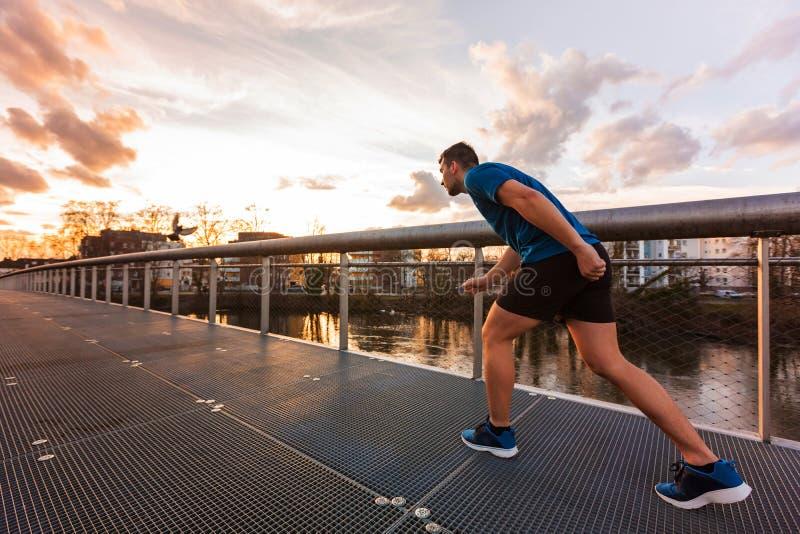 El hombre atlético joven se prepara para un sprint corrido imagen de archivo libre de regalías
