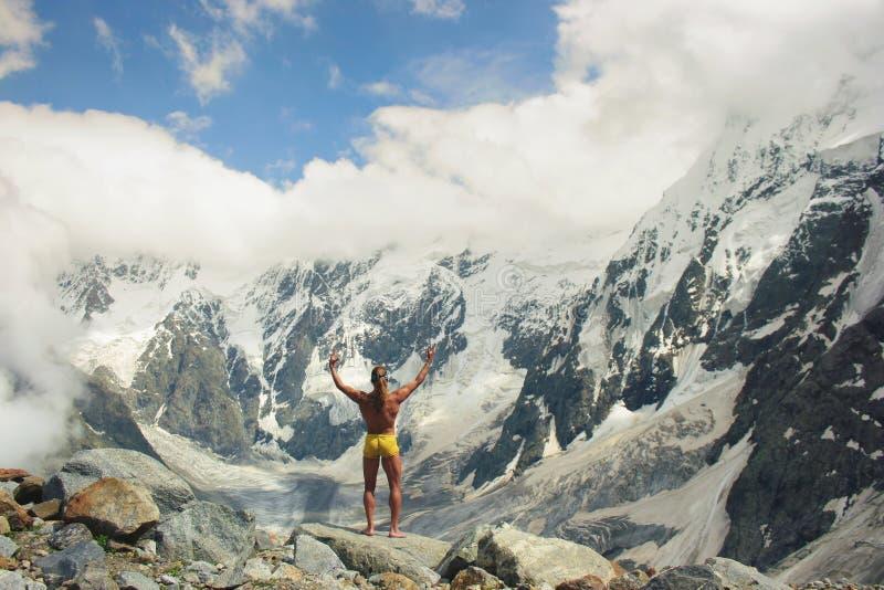 El hombre atlético se coloca en la gran altura delante de las montañas fotografía de archivo
