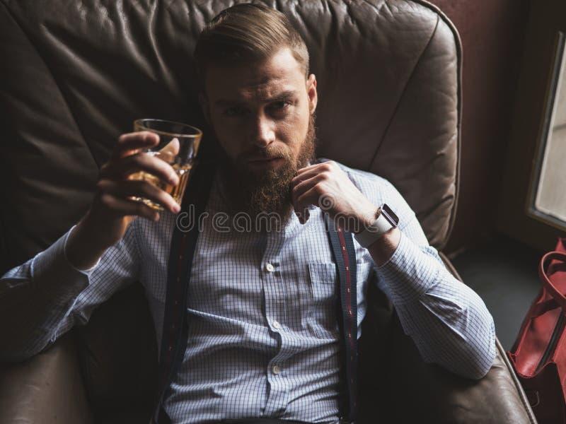 El hombre atractivo con la barba está descansando en casa imagenes de archivo