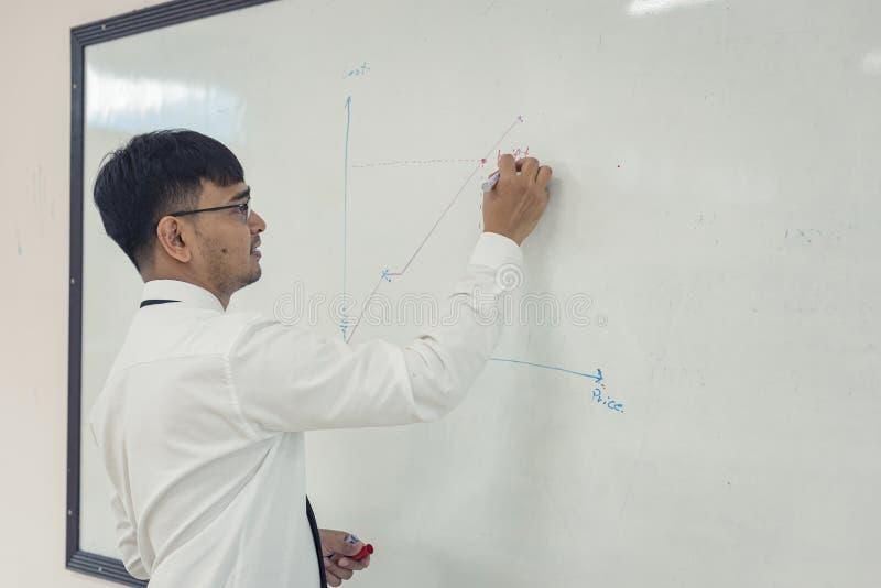 El hombre atractivo joven está escribiendo un plan empresarial en whiteboard imagen de archivo