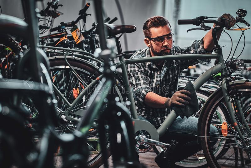El hombre atractivo ocupado en vidrios protectores está limpiando la bicicleta de la suciedad fotos de archivo