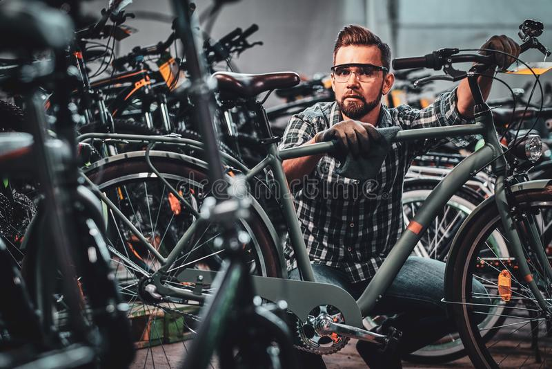 El hombre atractivo ocupado en vidrios protectores está limpiando la bicicleta de la suciedad imagenes de archivo