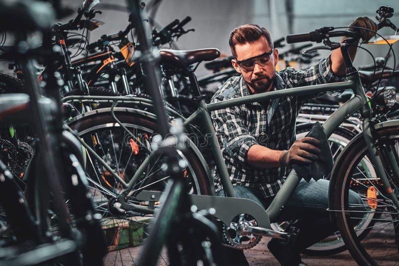 El hombre atractivo ocupado en vidrios protectores está limpiando la bicicleta de la suciedad imagen de archivo libre de regalías