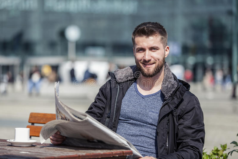El hombre atractivo se está sentando en una cafetería que lee el periódico imagen de archivo libre de regalías