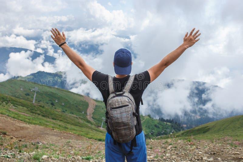 El hombre aumentó las manos para arriba en paisaje de la montaña Libertad y despreocupado imágenes de archivo libres de regalías