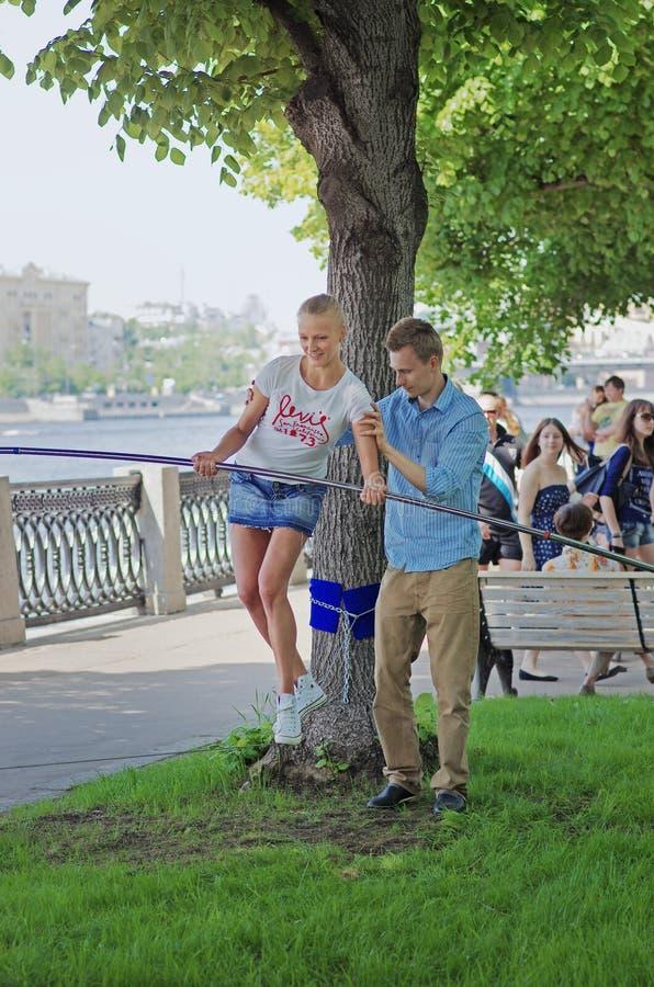 El hombre ayuda a la mujer joven en equilibrio durante su paseo de la cuerda tirante en el parque Gorkogo en Moscú fotos de archivo libres de regalías