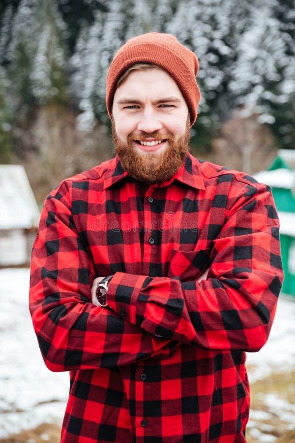 El hombre barbudo alegre que se colocaba con las manos dobló en invierno fotografía de archivo