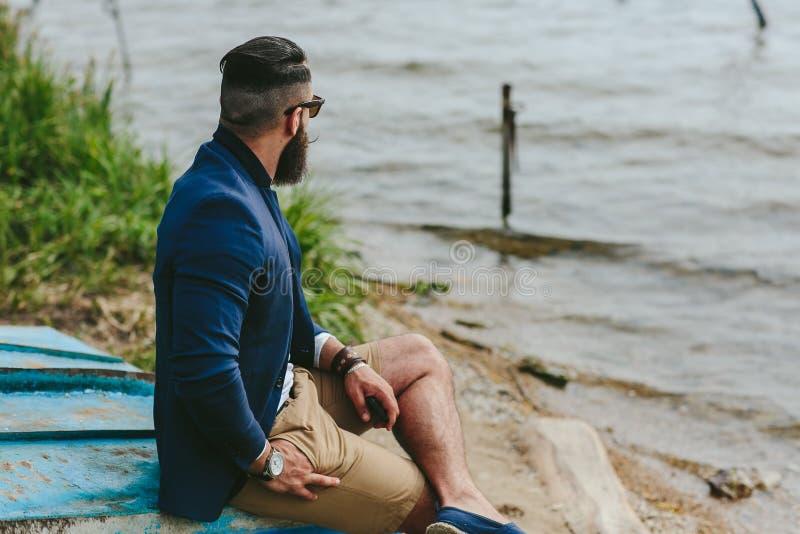 El hombre barbudo americano mira en la orilla del río imagenes de archivo