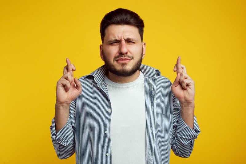 El hombre barbudo atractivo cierra ojos con esperanza grande, cruza los fingeres como cree en algo importante, aislado encima imágenes de archivo libres de regalías