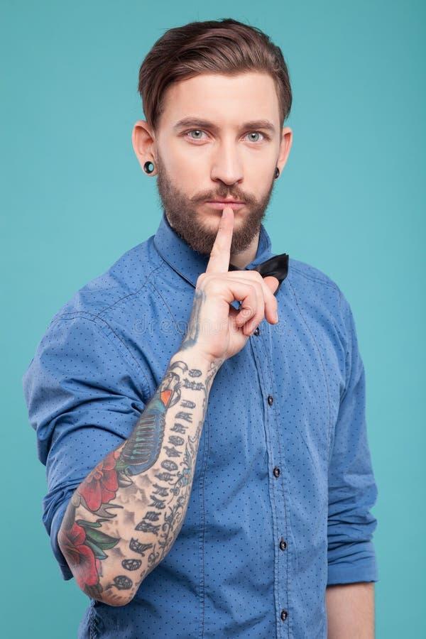 El hombre barbudo atractivo está pidiendo silencio imagen de archivo libre de regalías