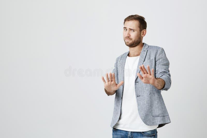 El hombre barbudo atractivo hace gesto asustado con las palmas, se defiende alguien, pide pararlo inmediatamente imagen de archivo