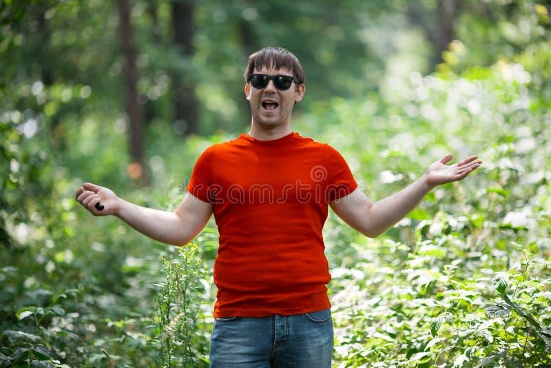 El hombre barbudo blanco en camiseta roja y en gafas de sol vaping un cigarrillo electrónico en el bosque foto de archivo libre de regalías
