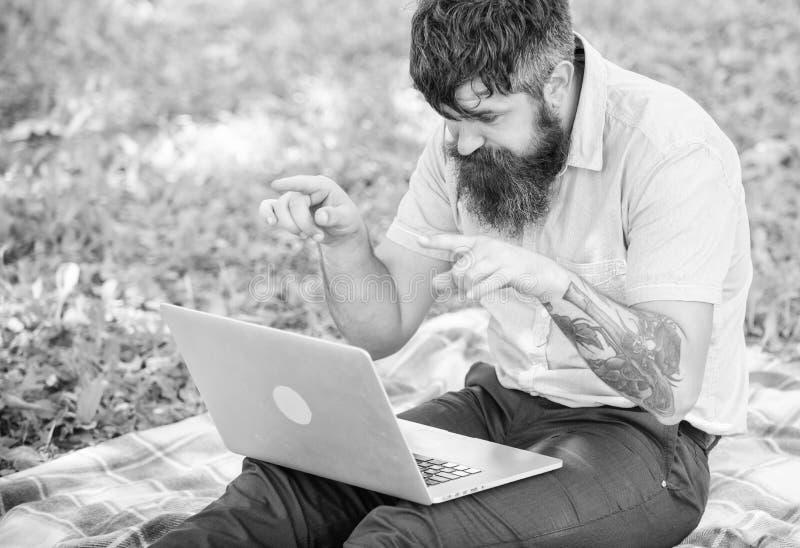 El hombre barbudo con el ordenador portátil sienta el fondo de la naturaleza del prado Escritor que busca el ambiente de la natur imagen de archivo