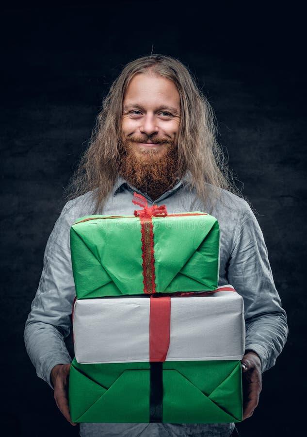 El hombre barbudo con el pelo largo sostiene la actual caja foto de archivo libre de regalías