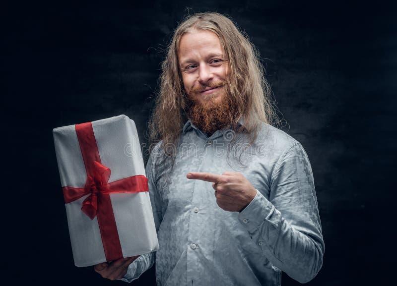 El hombre barbudo con el pelo largo sostiene la actual caja fotografía de archivo libre de regalías