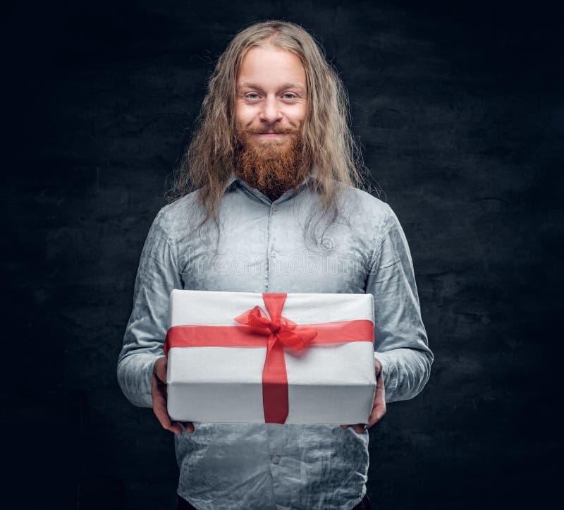El hombre barbudo con el pelo largo sostiene la actual caja fotos de archivo libres de regalías
