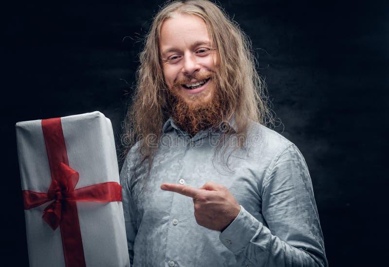 El hombre barbudo con el pelo largo sostiene la actual caja imágenes de archivo libres de regalías