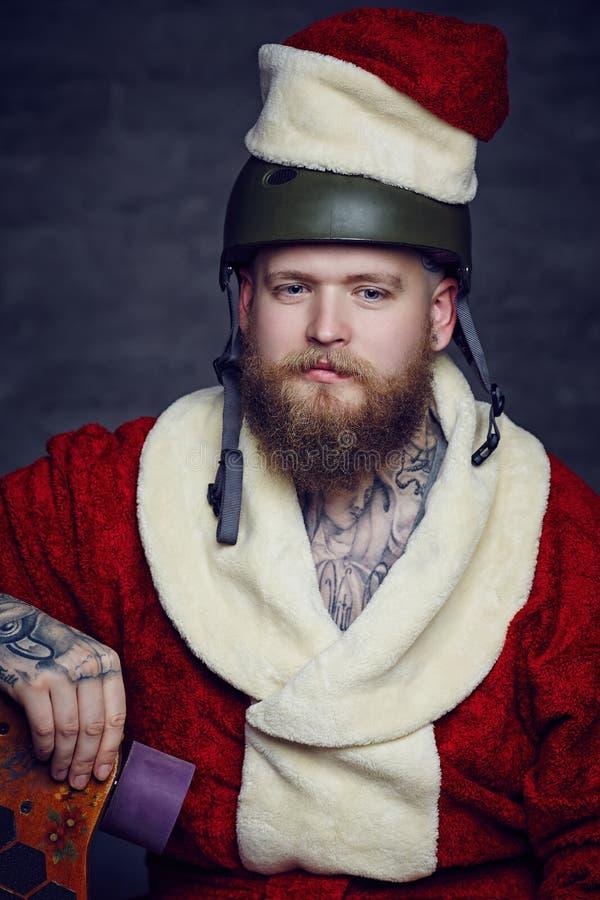 El hombre barbudo de Tattoed en el ` s de Papá Noel viste fotografía de archivo