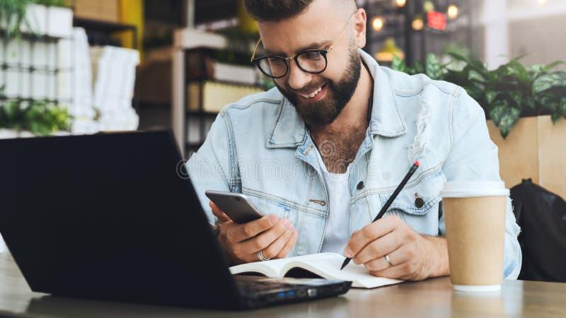 El hombre barbudo del inconformista se sienta en la tabla delante del ordenador portátil y escribe en el cuaderno, estudiante se  imagen de archivo
